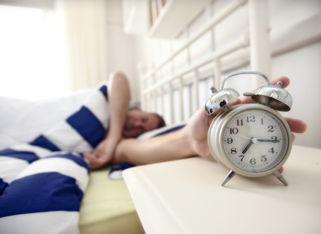 Man reaching for alarm clock